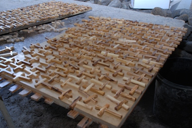 Olive wood crosses are laid on a table to dry after a sealant has been applied to them